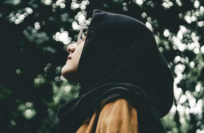 Young Muslim woman looking upwards in a forest.